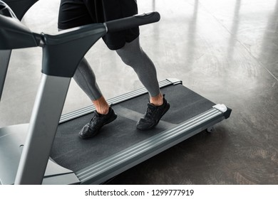 low section of athletic young man in sportswear running on treadmill in gym