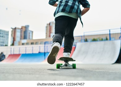 Low section back view portrait of contemporary young man riding skateboard outdoors in extreme park, copy space
