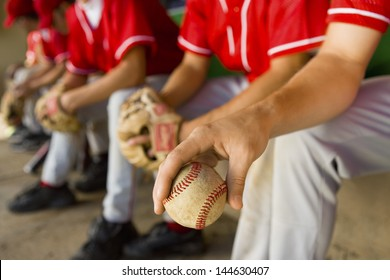 Low section of baseball team mates sitting in dugout with player holding a ball in foreground