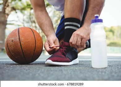 Low section of basketball player tying shoelace while crouching in court