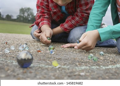 Low section of brother and sister playing marbles on playground