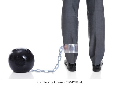 Low section of businessman with ball and chain attached to leg against white background