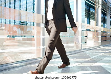 Low section of a businessman walking passed a modern glass office building in the city, carrying a financial newspaper in his hand.