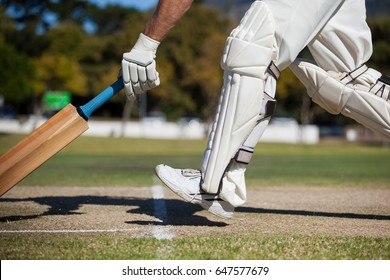 Low section of cricket player scoring run on field during sunny day