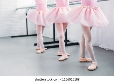 low section of cute little kids in pink tutu skirts and ballet shoes dancing in studio