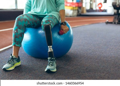 Low section of disabled active senior Caucasian woman with leg amputee exercising with dumbbell while sitting on exercise ball in fitness studio. Strong active senior female amputee training and