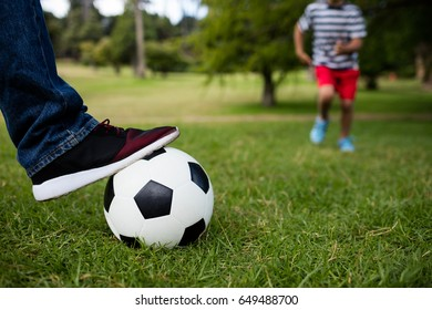 Low section of father and son playing football in park