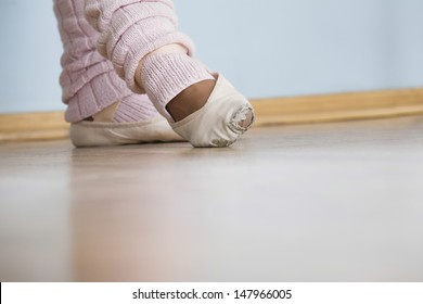 Low section of feet of female ballerina in rehearsal room