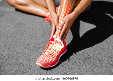 Low section of female athlete suffering from joint pain on track during sunny day