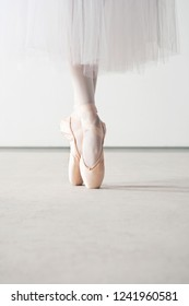 Low section of female classical ballet dancer feet on point shoes with white tutu on stage, indoors. Conceptual balance harmony training artistic discipline, coordinating movement, leisure lifestyle.