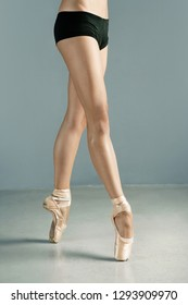 Low section of female classical ballet dancer legs and feet on point shoes on stage, indoors. Conceptual strength, balance, harmony, training artistic discipline, coordinating movement, lifestyle.