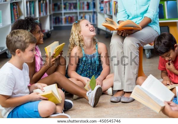 Baja sección de profesora con niños sonrientes leyendo libros en la biblioteca