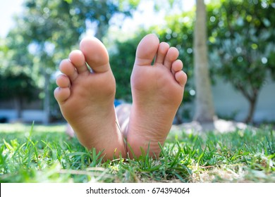 Low section of girl lying on grassy field in back yard