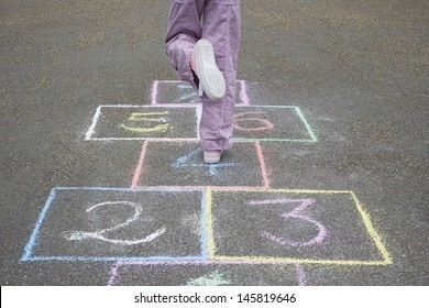 Low section of girl playing hop-scotch in playground