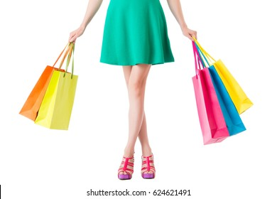 low section of green dress woman with hands showing lot of shopping bags cross the leg isolated on the white background with copyspace in empty area.