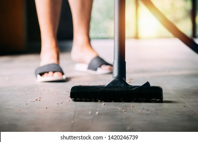 Low section of human legs wearing sandals using industrial electronic vacuum cleaner to hoover inside the house with plenty of dust and dirt - cleanliness and housekeeping concept