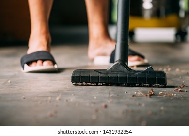 Low section of human legs wearing sandals using vacuum cleaner to clean inside the house with dust and dirt - cleanliness and housekeeping concept