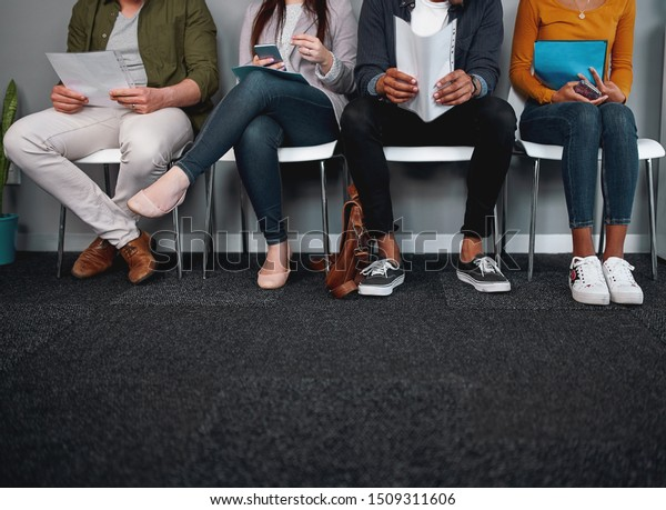 Low section of job applicants waiting in corridor preparing for recruiting process - photo of diverse feet sitting in a row waiting for job interview