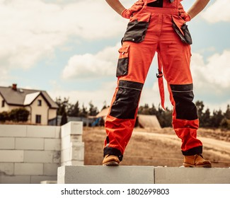 Low section legs of construction worker wearing workwear trousers and brown leather work boots standing on airbrick wall.