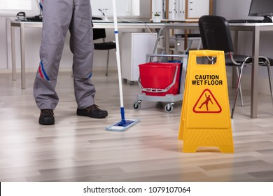 Low Section Of Male Cleaner Standing In Office With Mop And Caution Wet Floor Sign