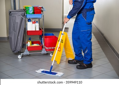 Low section of male janitor with broom cleaning office corridor
