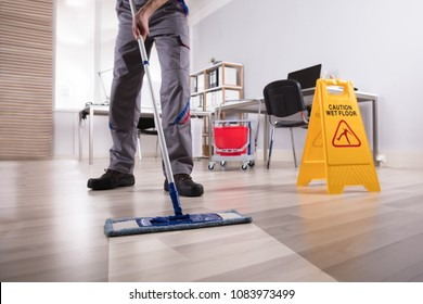 Low Section Of Male Janitor Cleaning Floor With Caution Wet Floor Sign In Office