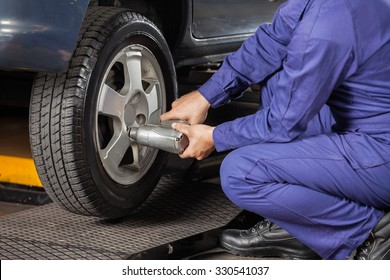 Low section of male mechanic screwing car tire with pneumatic wrench at garage