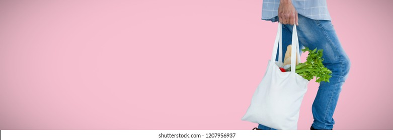 Low section of man carrying vegetables in shopping bag against pink background