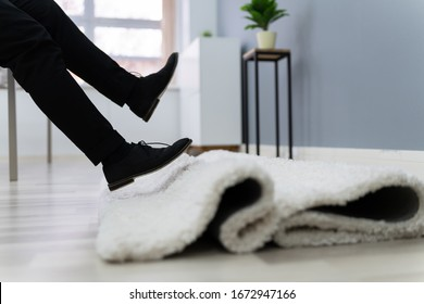 Low Section Of Man Legs Stumbling With A Carpet In The Living Room At Home