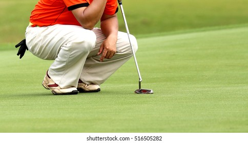 Low section of man squatting to line up his putt in golf course