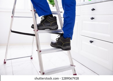 Low Section Of Man Stepping On Steel Ladder