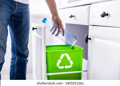 Low Section Of Man Throwing Empty Plastic Bottle In Recycling Bin In The Kitchen