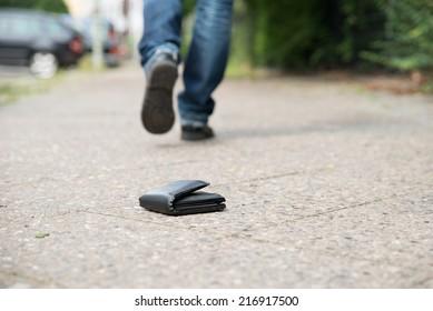 Low section of man walking against fallen wallet on street