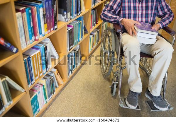 Sección baja de un hombre en silla de ruedas por estantería en la biblioteca