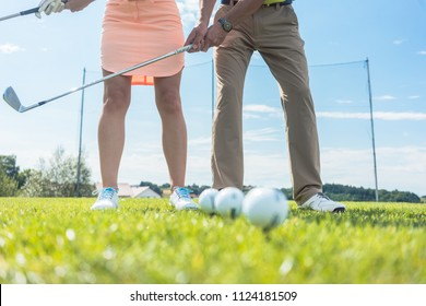 Low section of man and woman holding iron clubs, while practicing together the correct grip and move for playing golf on the green grass of a professional ground
