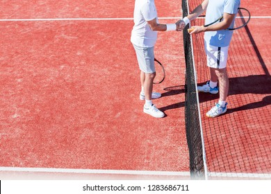 Low section of men shaking hands while standing by tennis net on red court during match