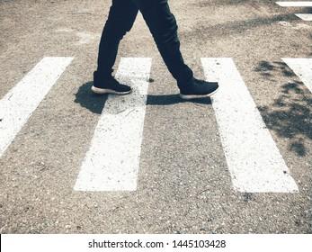 Low section of a pedestrian walking on crosswalk