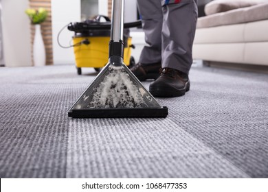 Low Section Of A Person Cleaning The Carpet With Vacuum Cleaner In Living Room