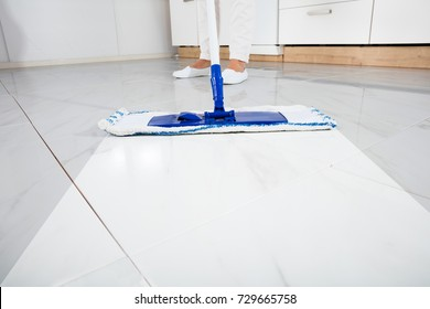 Low Section Of Person Wiping Floor With Mop In Kitchen Room