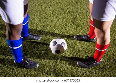 Low section of players standing by soccer ball on playing field at night