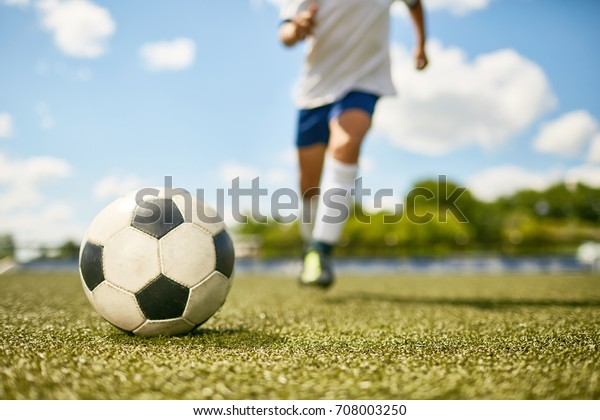 Low section portrait of unrecognizable teenage boy kicking ball during football practice, focus on ball lying on grass