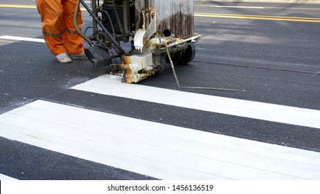 Low section of road worker using thermoplastic spray road marking machine to painting pedestrian crosswalk on asphalt road surface in the city