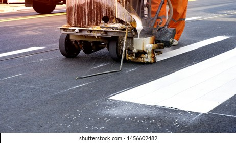 Low section of road worker using thermoplastic spray road marking machine to painting pedestrian crosswalk on asphalt road surface in the city, construction concept
