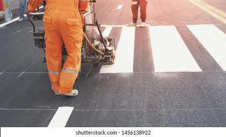 Low section of road workers using thermoplastic spray road marking machine to painting pedestrian crosswalk on asphalt road surface in the city