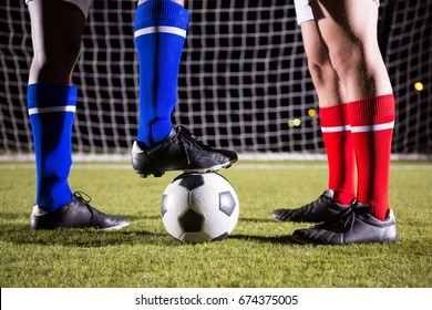 Low section of soccer players with ball on field against goal post