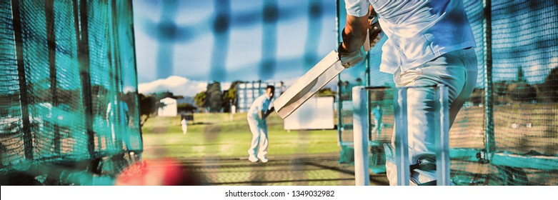 Low section of sportsman playing cricket at field on sunny day