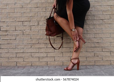 Low section of stylish woman wearing high heals and holding leather bag in front of brick wall , fashion concept