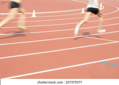 Low section of two athletes sprinting at the stadium, blurred motion, focus on the sports track