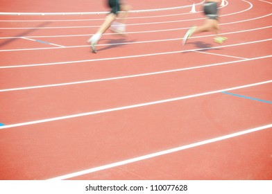 Low section of two track and field caucasian athletes sprinting at the stadium outdoors