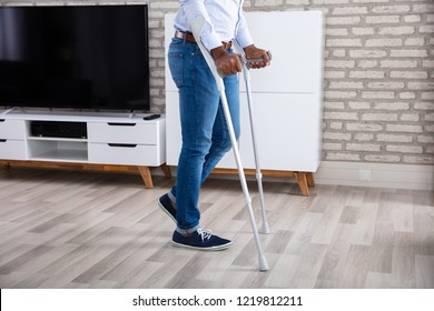 Low Section View Of A Disabled Man Walking With Crutches At Home